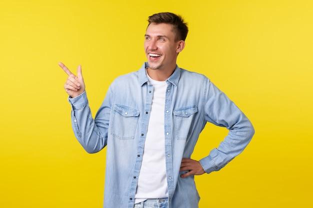 Knappe vrolijke blonde man, breed glimlachend en lachend over grappige promobanner, wijzend en tevreden naar de linkerbovenhoek kijkend, reclame voor evenement tonend, staande gele achtergrond.