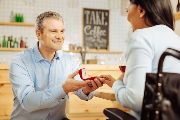 Knappe, vrolijke blonde man die lacht en zijn geliefde donkerharige gehandicapte vrouw voorstelt en een ring vasthoudt tijdens een romantisch diner