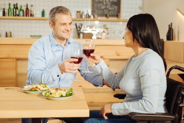 Knappe vrolijke blonde man glimlachend en een geïnspireerde gehandicapte donkerharige vrouw die glimlacht en wijn drinkt en eet