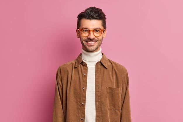 Knappe vrolijke europese man met dikke haren glimlacht breed