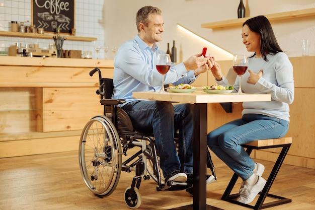 Knappe, vrolijke gehandicapte man die lacht en zijn mooie geliefde geïnspireerde vrouw voorstelt en een ring vasthoudt tijdens een romantisch diner