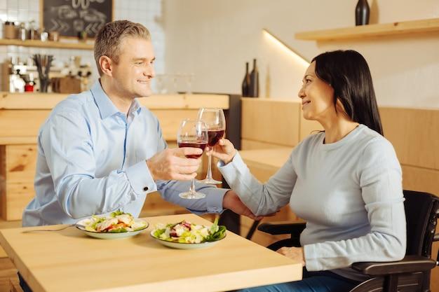 Knappe vrolijke, goed gebouwde man en een behoorlijk geïnspireerde gehandicapte vrouw die lacht en wijn drinkt en aan het eten is