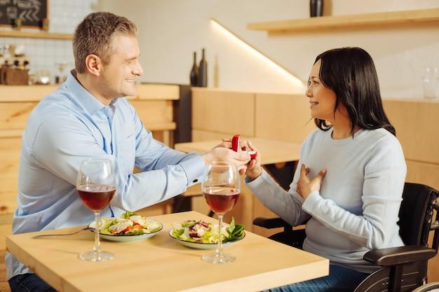 Knappe vrolijke goedgebouwde man die lacht en zijn mooie geïnspireerde gehandicapte vrouw voorstelt terwijl hij een ring vasthoudt en eet