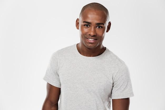 Knappe vrolijke jonge afrikaanse man geïsoleerd staan