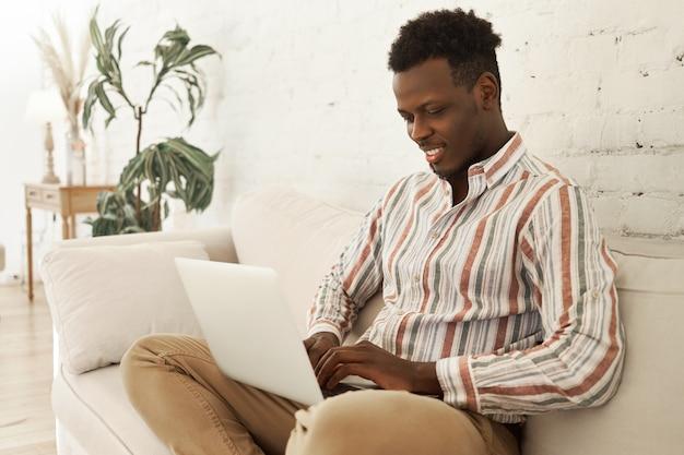 Knappe vrolijke jonge donkere mannelijke smm manager genieten van werken vanuit huis zittend op de bank met laptopcomputer