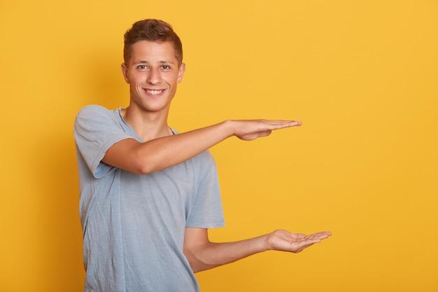 Knappe vrolijke jonge man gebaar maken, maatregel tonen