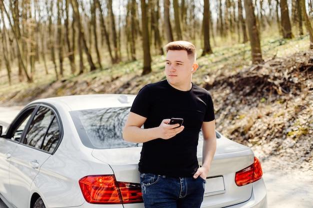 Knappe, vrolijke, jonge man gebruikt smartphone in auto en buitenshuis