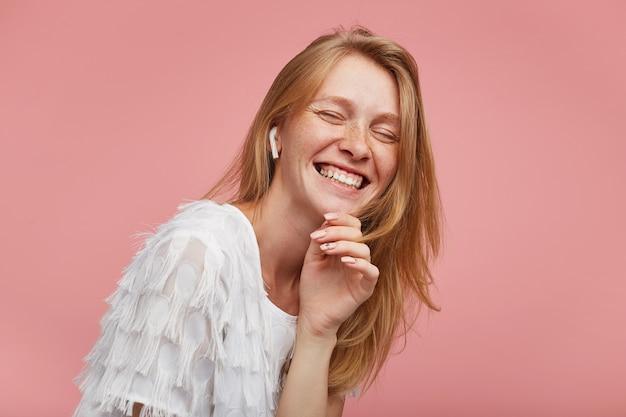 Knappe vrolijke jonge roodharige dame met natuurlijke make-up die haar kin met opgeheven hand vasthoudt en vrolijk lacht met gesloten ogen, geïsoleerd op roze achtergrond