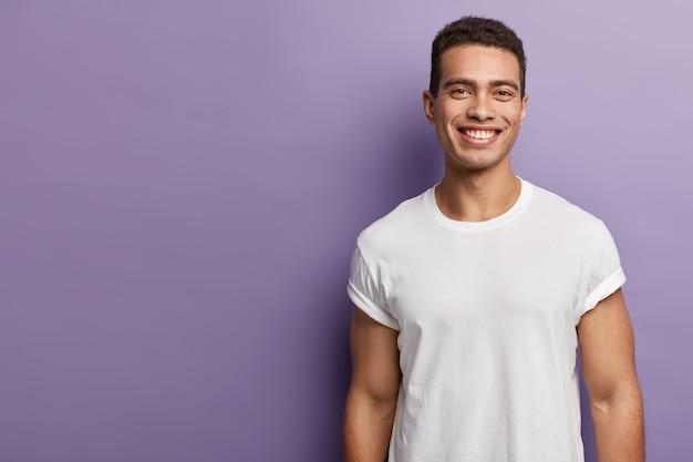 Knappe, vrolijke jonge sportman heeft een sportief lichaam, gespierde armen, draagt een wit mock-up t-shirt, heeft kort donker haar, een brede aantrekkelijke glimlach, staat over de paarse muur, lege kopie ruimte opzij