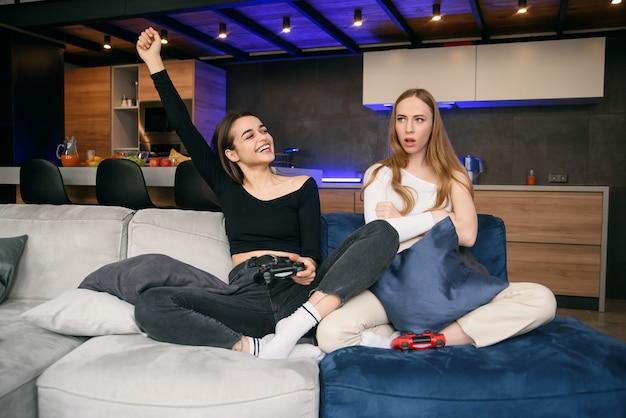 Knappe vrolijke jonge vriendinnen zitten op de bank in het moderne appartement en genieten van videogames