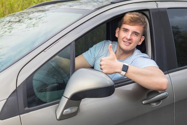 Knappe vrolijke kerel, bestuurder, jonge positieve man, die zijn auto drijft, glimlachend toont duim omhoog, zoals gebaar van autoraam. tevreden koper, klant van een nieuwe auto die geniet van het rijden. goede koop, aankoop