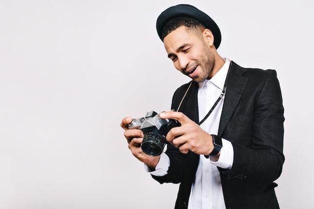 Knappe vrolijke kerel in pak, hoed die in handen kijkt. reizen, toeristen, plezier maken, retrostijl, echte emoties.