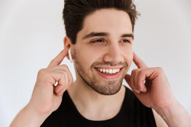 Knappe vrolijke lachende gelukkige jonge sportman geïsoleerd over witte muur luisteren muziek met oortelefoons.