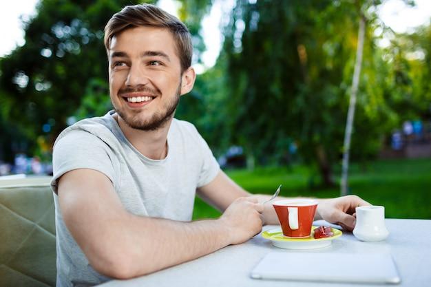 Knappe vrolijke lachende jonge man zit aan de tafel in de open lucht cafe met een kopje koffie.