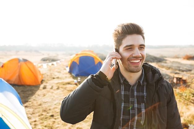 Knappe vrolijke man buiten kamperen, praten op mobiele telefoon
