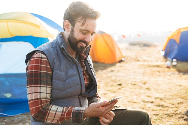 Knappe vrolijke man die buiten kampeert, met behulp van mobiele telefoon