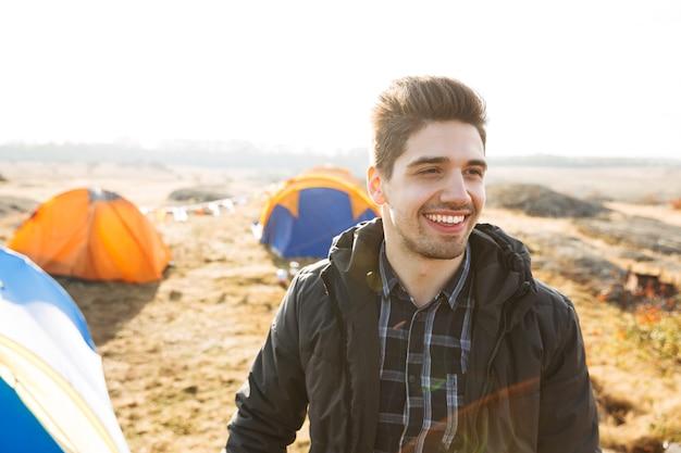 Knappe vrolijke man die buiten kampeert