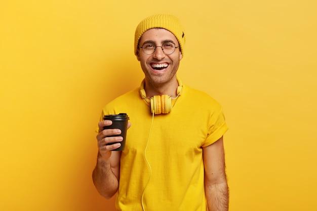 Knappe vrolijke man gebruikt koptelefoon houdt afhaalmaaltijden koffie, in goed humeur