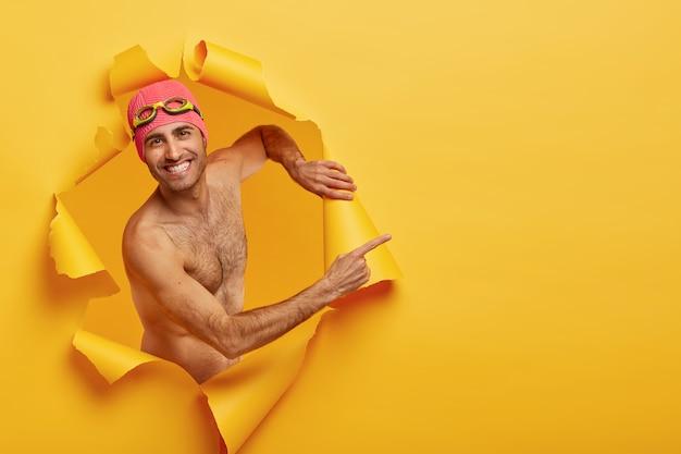 Knappe vrolijke man recreëert tijdens zomervakanties, maakt creatieve foto, poseert in gescheurd gescheurd papiergat