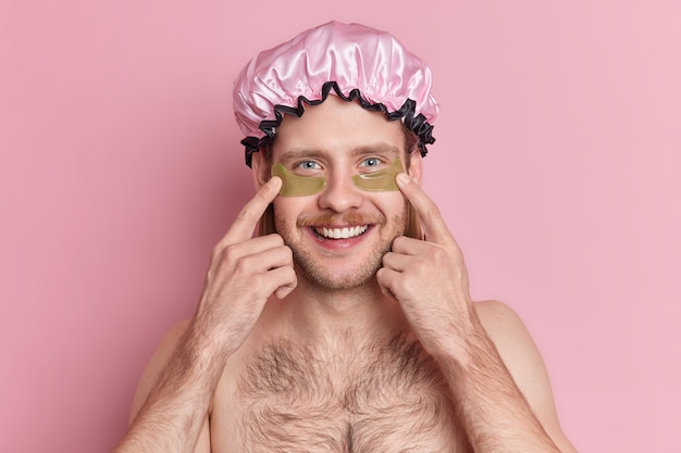 Knappe vrolijke ongeschoren man geeft aan dat hydrogelpleisters onder de ogen rimpels vermindert en een blije glimlach op het gezicht heeft