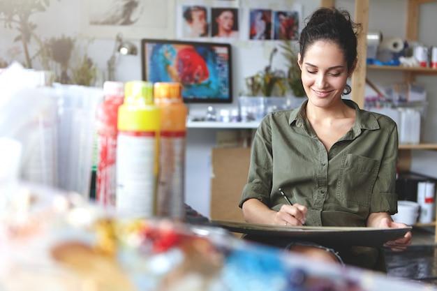 Knappe vrolijke professionele jonge vrouwelijke kunstenaar die aan een nieuw creatief project werkt, tekenen, schetsen maken met potlood, zich geïnspireerd voelen. mensen, baan, beroep, beroep en hobby concept