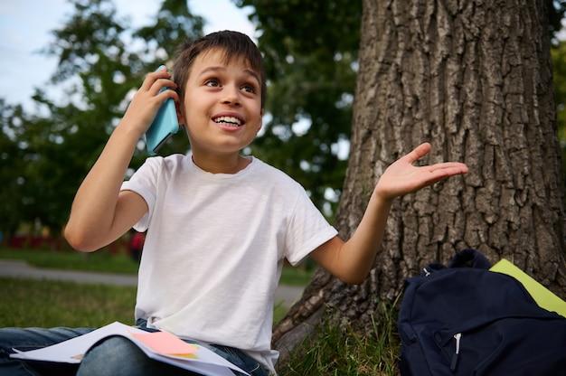 Knappe vrolijke schattige schoolkindjongen praten op mobiele telefoon, schattig lachend wegkijkend, gebarend met handen, rustend op het openbare park na de eerste dag op school op een mooie zomerdag.
