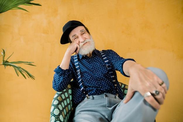 Knappe vrolijke trendy senior man met goed verzorgde baard, gekleed in donkerblauw shirt, bretels, grijze broek en zwarte hipster cap, zittend in stoel in studio voor gele muur
