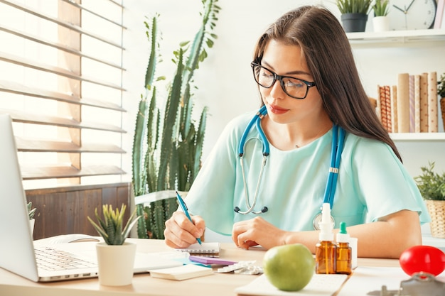 Knappe vrouw artsenzitting bij haar lijst in medisch bureau
