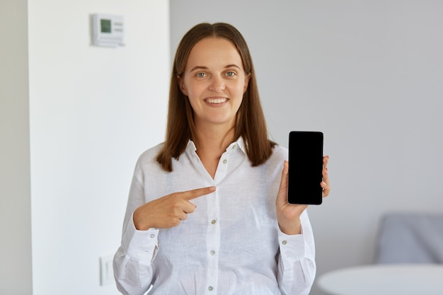 Knappe vrouw die een wit overhemd draagt dat een smartphone in handen houdt en met een wijsvinger naar het lege scherm wijst, kijkend naar de camera met een charmante glimlach.