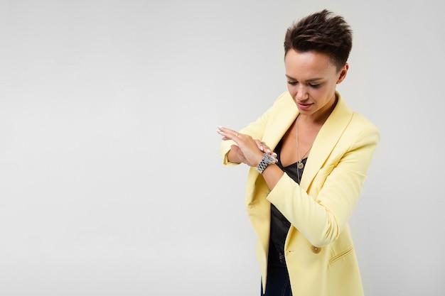 Knappe vrouw die in gele blazer en zwarte kleding geïsoleerde tijd bekijkt