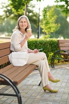 Knappe vrouw die koffie drinkt op een parkbank