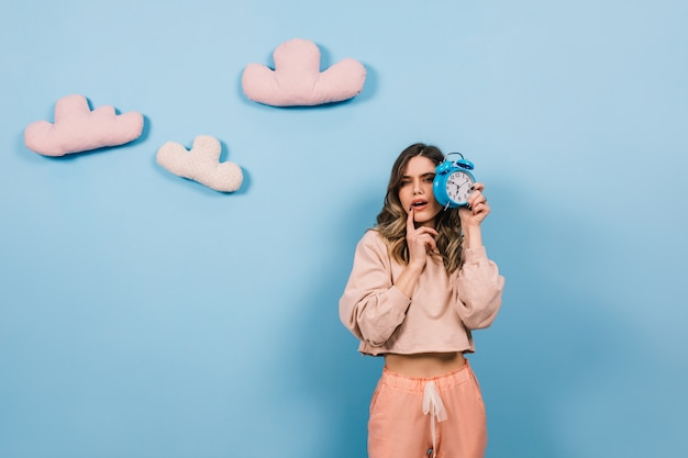 Knappe vrouw die zich voordeed op blauwe muur met wolken