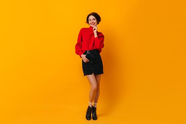 Knappe vrouw in rode sweater die zich op gele muur bevindt