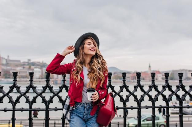 Knappe vrouw in spijkerbroek en elegante hoed poseren onder grijze lucht aan de kade