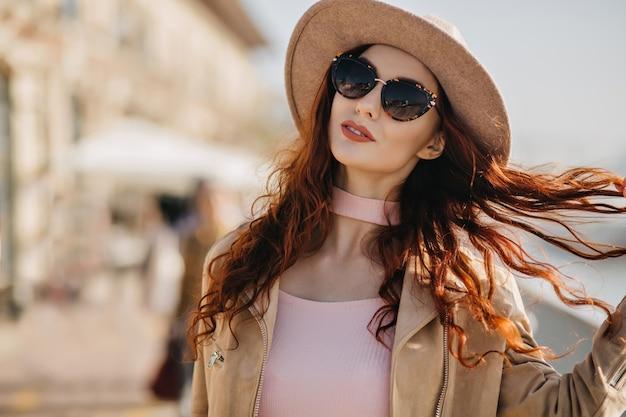 Knappe vrouw in zwarte zonnebril speelt met rood krullend haar