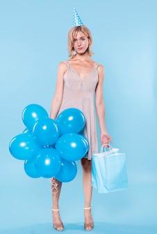 Knappe vrouw met ballonnen en papieren zakken