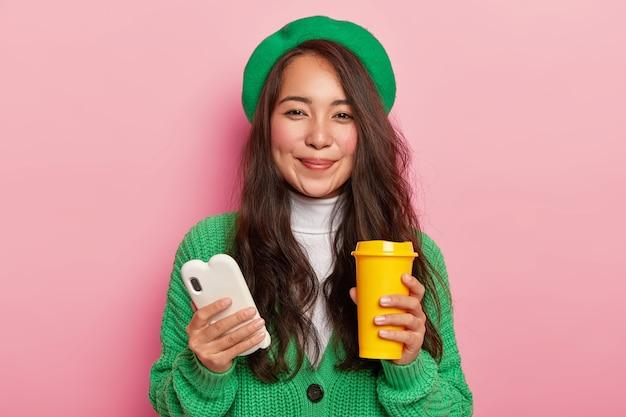 Knappe vrouw met donker steil haar, rode wangen houdt witte mobiele telefoon en koffiekopje vast, geniet van vrije tijd om te surfen op sociale netwerken