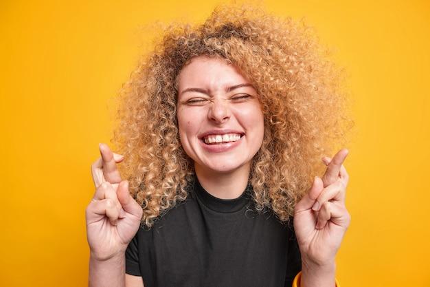 Knappe vrouw met krullend borstelig haar glimlacht breed houdt vingers gekruist heeft hoop op beter