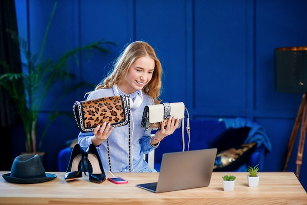Knappe vrouwelijke blogger die handtas twee bespreken terwijl het schieten van blog over mode.