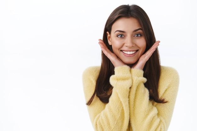 Knappe vrouwelijke brunette vrouw met perfecte stralende glimlach en geen vlekken make-up huid, haar gezicht aanraken en er tevreden uitzien, verlost van acne