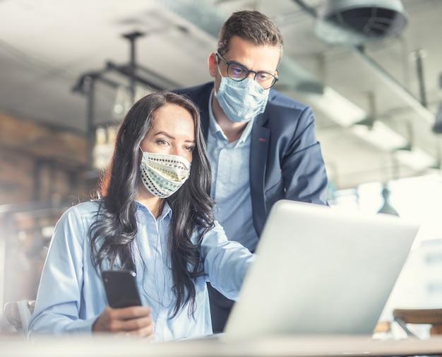 Knappe vrouwelijke en mannelijke collega's kijken samen naar het computerscherm en dragen gezichtsmaskers.