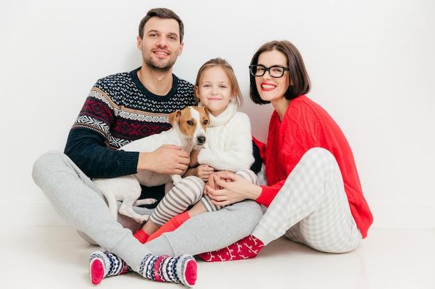 Knappe vrouwelijke en mannelijke zitten samen met hun dochter en jack russell terrier hond
