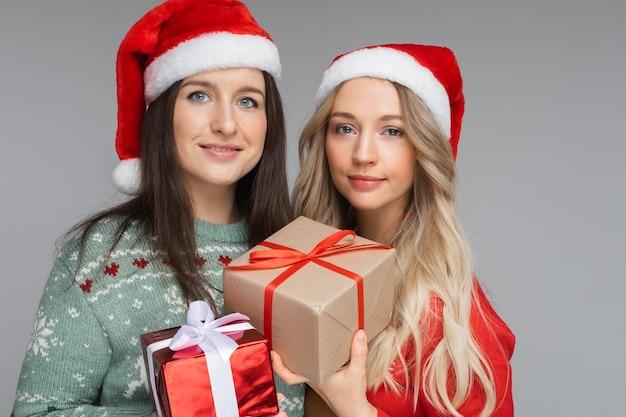 Knappe vrouwenvrienden in rode en witte kerstmutsen houden een cadeautje voor elkaar vast en glimlachen