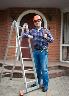 Knappe werknemer poseren met gereedschap tegen huisingang