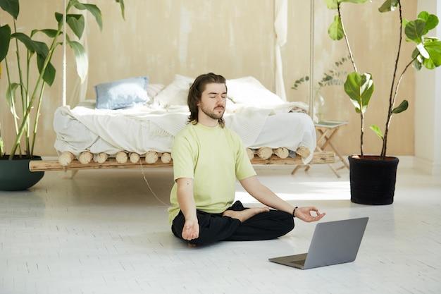 Knappe yogaleraar concentreren met gesloten ogen, mediteren met behulp van laptop voor het beoefenen van meditatie thuis