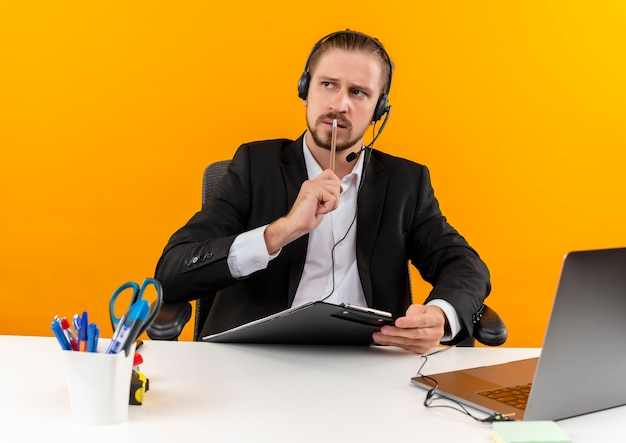 Knappe zaken man in pak en koptelefoon met een microfoon houden klembord opzij kijken verbaasd zittend aan de tafel in offise over oranje achtergrond