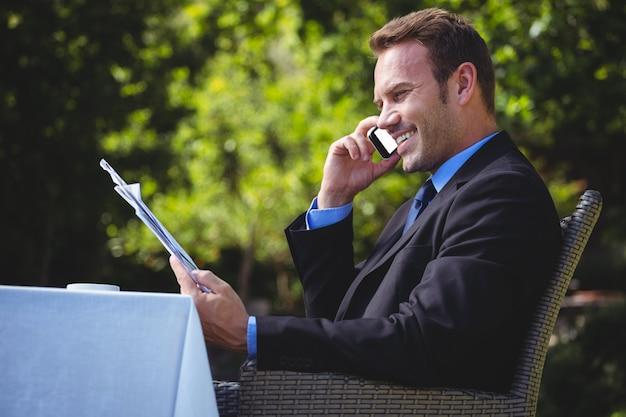 Knappe zakenman aan de telefoon en het lezen van het menu