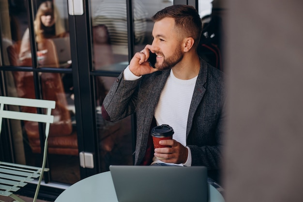 Knappe zakenman aan het werk op laptop in café