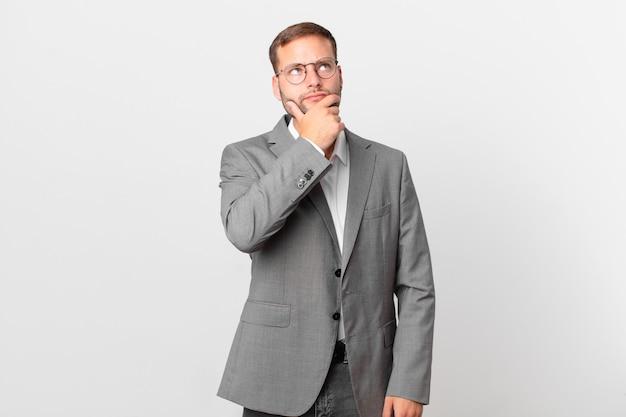 Knappe zakenman denkt, voelt zich twijfelachtig en verward
