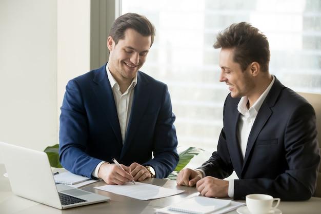 Knappe zakenman die contract met partner ondertekent